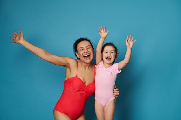Entzückende frau im roten badeanzug umarmt süßes kleines mädchen und hebt die hände auf blauem hintergrund