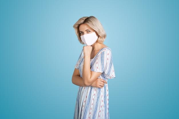 Entzückende frau mit blonden haaren, die eine weiße medizinische maske trägt, posiert vor der kamera an einer blauen wand bei s...