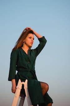 Entzückende frau mit braunem haar, die sich auf dem dach mit erstaunlich blauem himmel hinter sich entspannt
