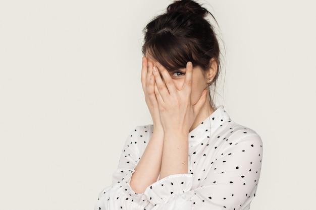 Entzückende frau mit brünetten haaren versteckt sich mit handflächen in die kamera und trägt ein weißes hemd auf einem stu...