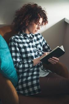 Entzückende frau mit lockigem haar schreibt in einem buch, während sie zu hause in einem sessel mit brille liegt