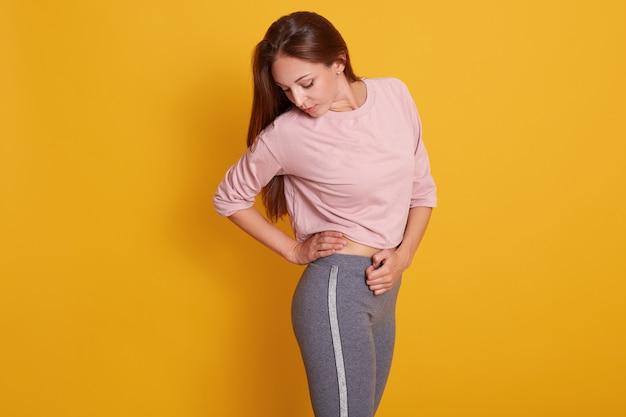 Entzückende frau mit perfektem körper in der sportkleidung lokalisiert auf gelbe, sportliche frau, die ergebnis ihrer harten arbeit betrachtet, dame mit gepumptem gesäß. sport- und fitnesskonzept