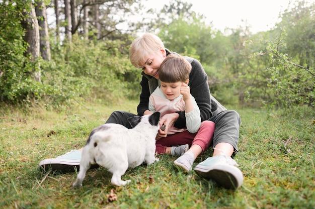 Entzückende frau und kleiner junge, die mit hund spielen