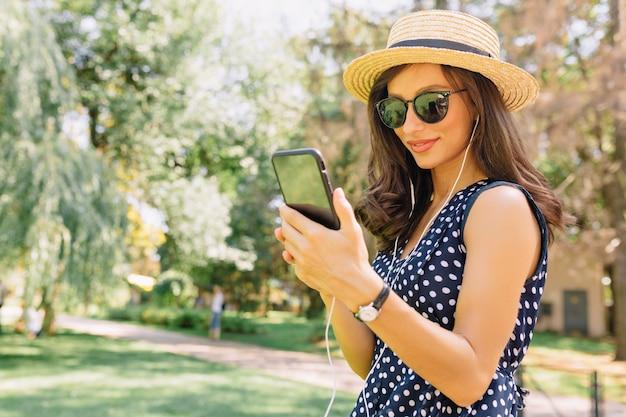 Entzückende frohe frau, die smartphone benutzt und das gehen im park genießt