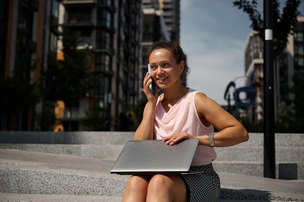 Entzückende gemischtrassige afroamerikanerfrau, die auf dem handy spricht und auf den stufen mit einem laptop auf dem städtischen hintergrund der hohen gebäude sitzt. geschäftsfrau in der mittagspause