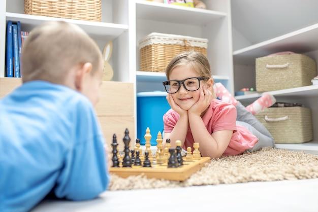 Entzückende geschwister, die auf dem boden liegen und schach miteinander spielen