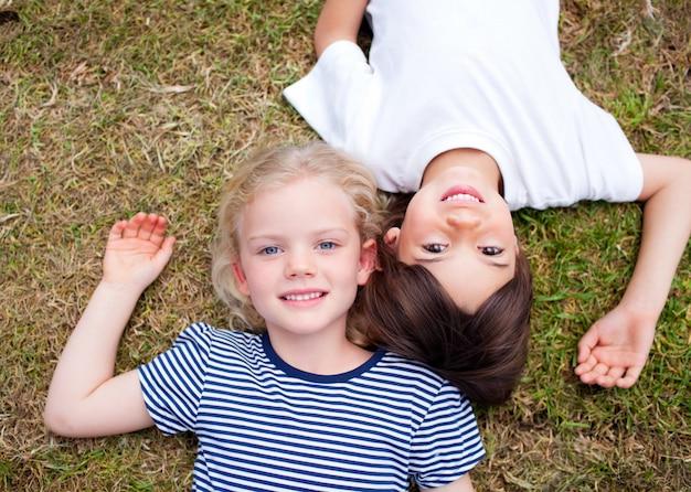 Entzückende geschwister, die auf dem gras liegen