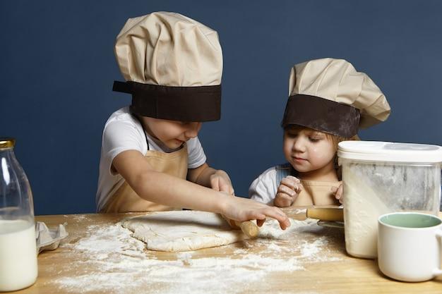 Entzückende geschwisterjungen und -mädchen, die zusammen kekse backen, am küchentisch mit flasche milch, mehl stehend, teig mit nudelholz abflachend. familie, kindheit, hausgemachte bäckerei, freude und glück