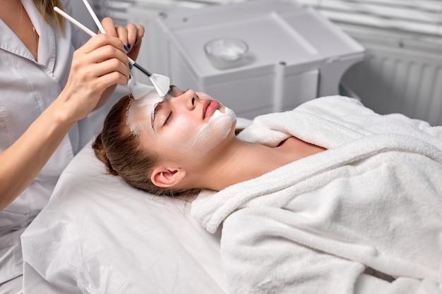 Entzückende hübsche frau, die entspannt auf der couch liegt und von einer kosmetikerin behandelt wird?