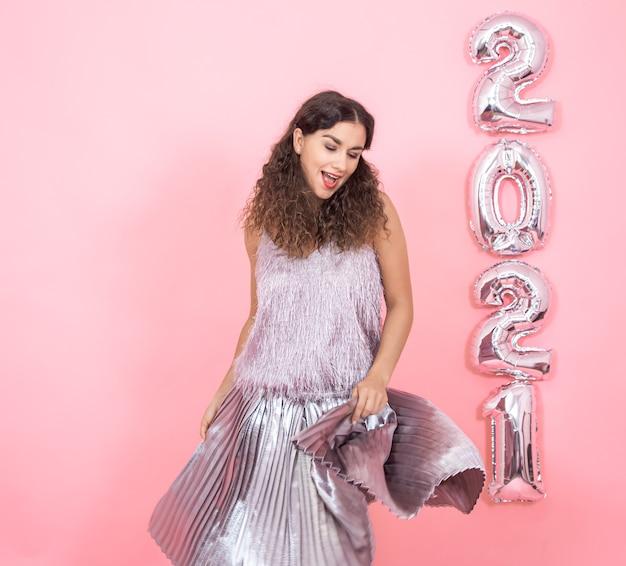 Entzückende junge brünette frau mit dem lockigen haar, das in festlichen kleidern auf einer rosa wand mit silbernen luftballons für das neujahrskonzept tanzt