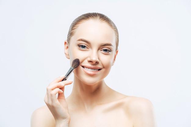 Entzückende junge brünette frau trägt kosmetische tongrundierung mit schönheitspinsel auf