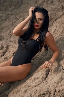 Entzückende junge dame, die nur in einem schwarzen body gekleidet ist und auf trockenem sand zwischen leerem steinbruch liegt?