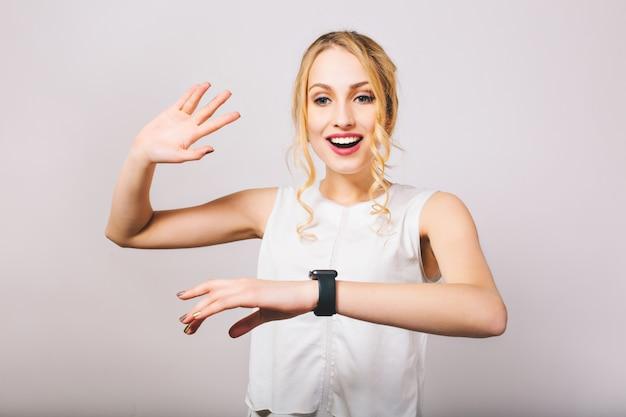 Entzückende junge dame mit eleganter frisur, die mit überraschtem gesichtsausdruck und hand aufwirft. wunderschönes lockiges blondes mädchen, das weiße bluse trägt, die neue schwarze armbanduhr zeigt