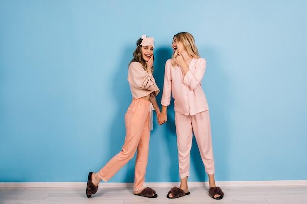 Entzückende junge damen in nachtwäsche, die auf blauer wand sprechen