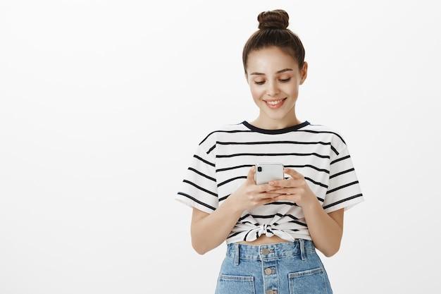 Entzückende junge frau, die am handy lächelt, erfreut beim ansehen von video, nachrichten oder unter verwendung der smartphone-anwendung