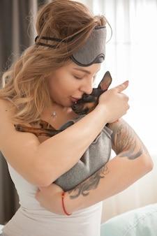 Entzückende junge frau, die ihren kleinen hund morgens nach dem aufwachen küsst.