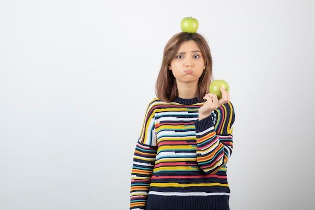 Entzückende junge frau in der freizeitkleidung, die grüne äpfel mit traurigem gesicht hält.