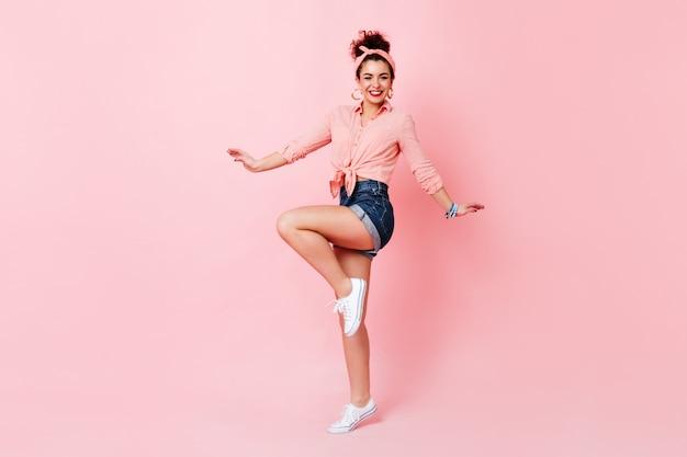 Entzückende junge frau in shorts, baumwollbluse und stirnband, die glücklich auf rosa raum springen.