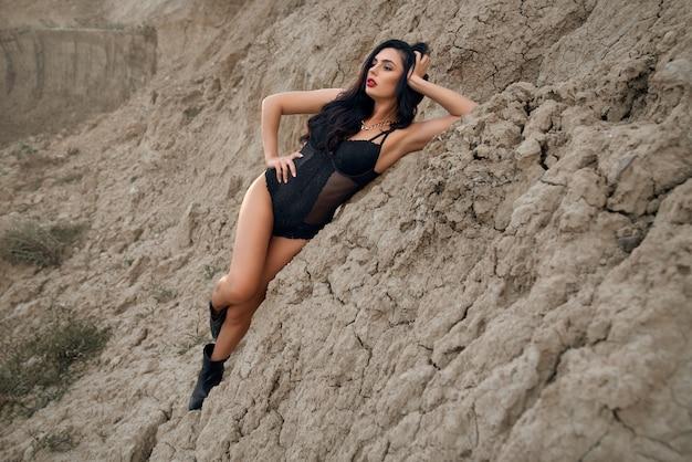 Entzückende junge frau in stilvoller schwarzer bodywear, die unter trockenem, leerem steinbruch posiert