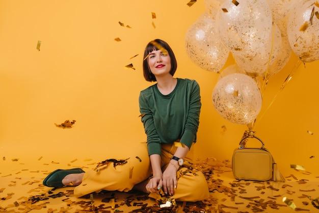 Entzückende junge frau mit kurzen haaren, die funkelndes konfetti betrachten. erfreutes weibliches model in trendiger kleidung, das neben heliumballons sitzt.