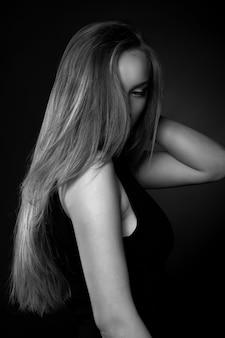 Entzückende junge frau mit langen glatten haaren trägt ein klassisches schwarzes kleid, das im schatten im studio posiert. schwarz-weiß-aufnahme