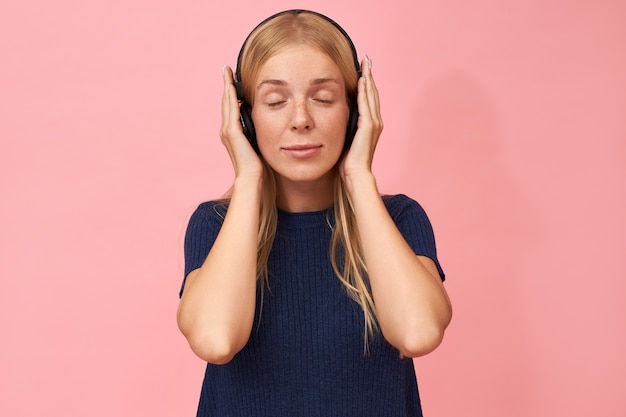 Entzückende junge kaukasische frau mit sommersprossen, die augen geschlossen halten, die neues album ihres lieblingsmusikkünstlers mit drahtlosen kopfhörern genießt