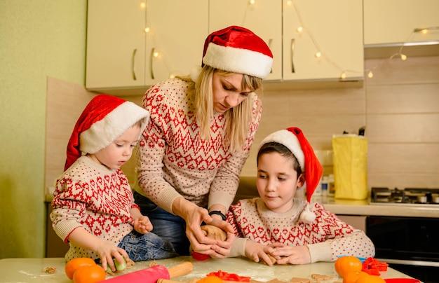 Entzückende jungen bereiten den teig vor und backen lebkuchen