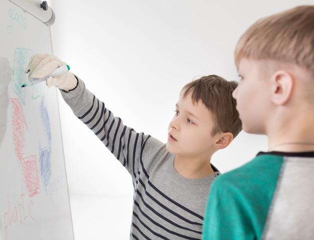 Entzückende jungen, die recyclingzeichen zeichnen