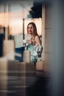 Entzückende kaukasische frau, die mit einer tasse kaffee sitzt und frühstückt