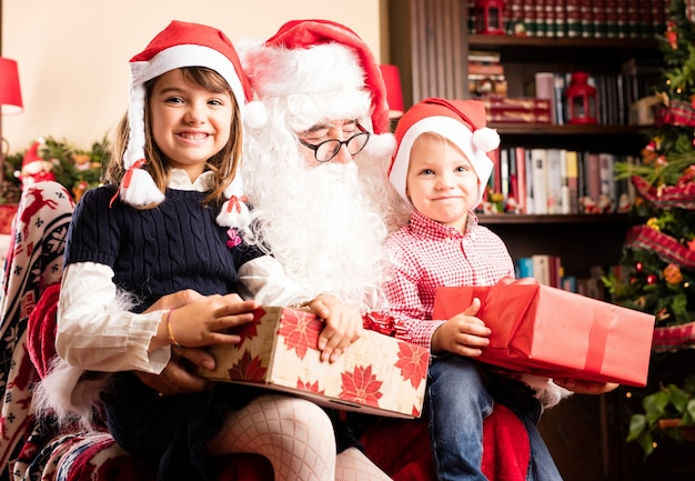 Entzückende kinder, die auf einem sankt beine auf weihnachten sitzen