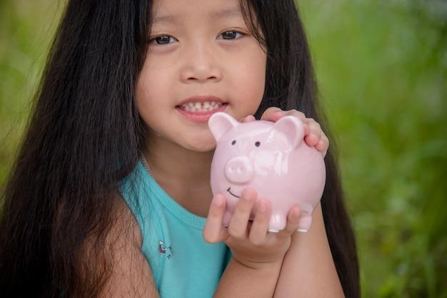 Entzückende kinder, die münzen im sparschwein sparen. glückliche kleine investition, die geld für die glückliche zukunft spart. mädchen lächeln mit glücklichem gesicht