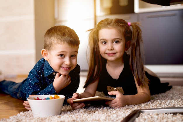 Entzückende kinder, die zusammen auf tab spielen und leckere gelige snacks haben