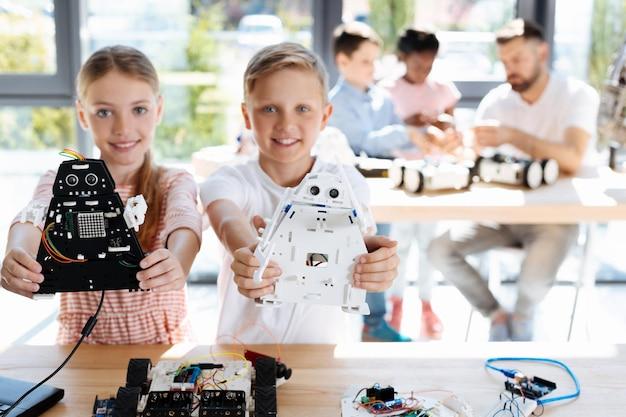 Entzückende kinder im teenageralter, die die werkstatt für roboterfahrzeuge inspizieren