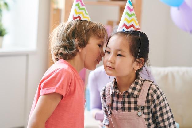 Entzückende kinder in geburtstagskappen spielen kindisches spiel, in dem man das gleiche wort miteinander flüstern sollte
