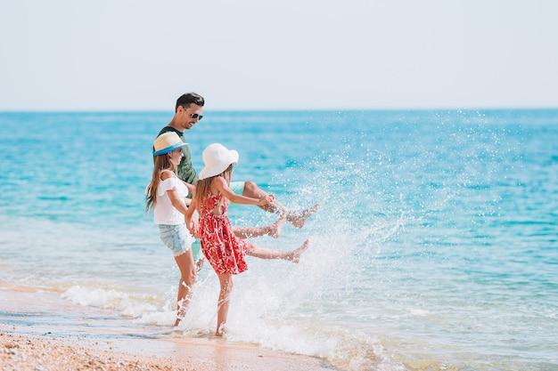 Entzückende kinder und ihr vater am strand während der sommerferien