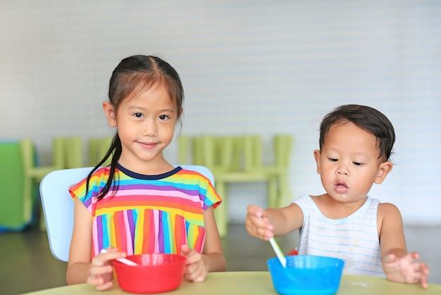 Entzückende kleine asiatische schwester und ihr kleiner bruder, die getreide mit corn-flakes und milch isst