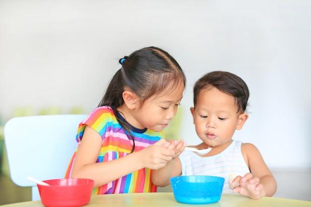 Entzückende kleine asiatische schwester und ihr kleiner bruder, die zusammen getreide mit corn-flakes und milch isst und auf dem tisch freundlich ist