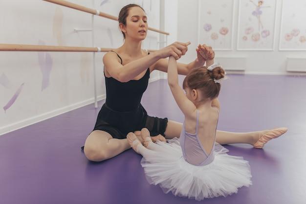 Entzückende kleine ballerina, die mit ihrem ballettlehrer an der tanzschule trainiert.