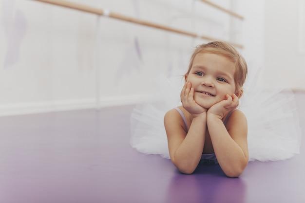 Entzückende kleine ballerina, die nach balletttanzkurs im studio ruht