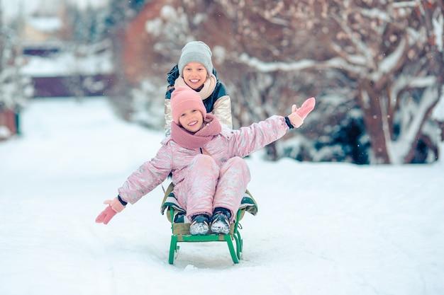 Entzückende kleine glückliche mädchen, die am schneebedeckten tag des winters rodeln.