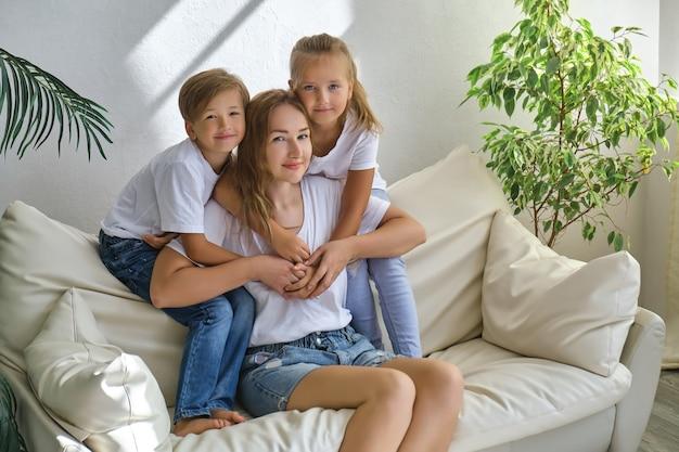 Entzückende kleine kinder, jungen und mädchen umarmen ihre mutter, während sie an einem sonnigen tag auf dem sofa im wohnzimmer sitzen