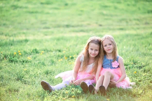 Entzückende kleine mädchen am frühlingstag draußen sitzend auf dem gras