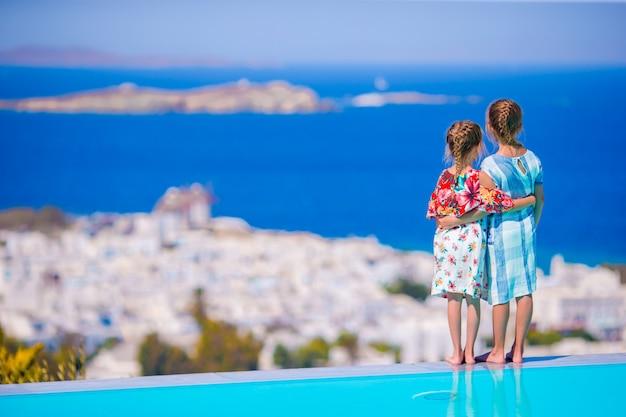 Entzückende kleine mädchen am rande des außenpools mit herrlichem blick auf berühmte sehenswürdigkeiten in griechenland
