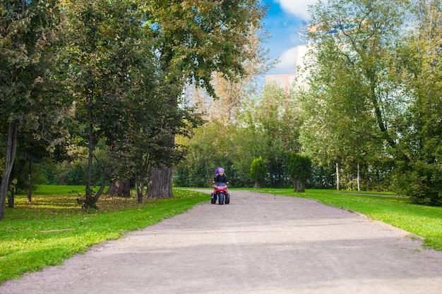 Entzückende kleine mädchen, die auf das motobike des kindes im grünen park fahren
