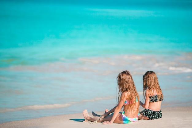 Entzückende kleine mädchen, die auf dem strand sich entspannen