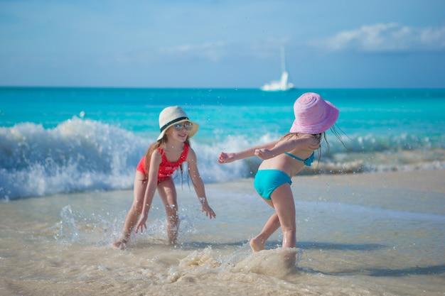 Entzückende kleine mädchen, die im seichten wasser am exotischen strand spielen