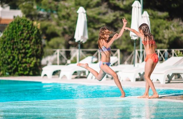 Entzückende kleine mädchen, die im urlaub im swimmingpool im freien spielen
