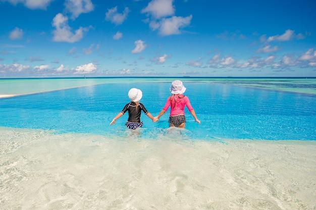Entzückende kleine mädchen, die im urlaub swimmingpool im freien spielen