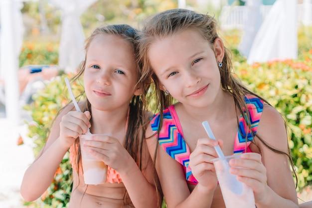 Entzückende kleine mädchen, die milchshake auf tropischem strand trinken