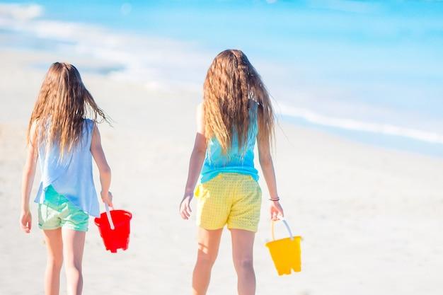 Entzückende kleine mädchen, die mit sand auf dem strand spielen. hintere ansicht von den kindern, die entlang den strand gehen